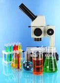 Reagenzgläser mit bunten flüssigkeiten und mikroskop auf blauem hintergrund — Stockfoto