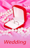 Snubní prsteny v červené pole na pozadí růžovou látkou — Stock fotografie