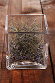 Dried herb in glass container on wooden table close-up — Stock Photo