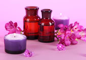 Spa oil and freesia on purple background — Stock Photo
