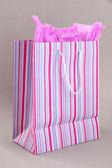 Striped shopping bag on grey background — Stock Photo