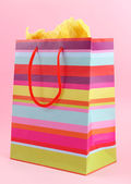 Striped shopping bag on pink background — Stock Photo