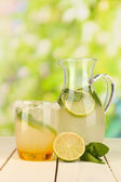 Citrus lemonade in pitcher and glass on wooden table on natural background — Stock Photo