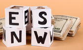 "White paper cubes labeled ""News"" with money on beige background — Foto de Stock"