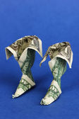 Dollar folded into boots on blue background — Stock Photo