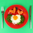 Sausages in form of hearts, scrambled eggs and parsley, on color plate, on color background - Stock Photo