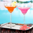 Glasses of cocktails on table near pool — Stock Photo #24668371