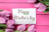 Beautiful bouquet of purple tulips and card on pink wooden background — Stock Photo