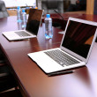 Empty conference room with laptops on table - Stock Photo