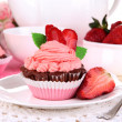 Beautiful strawberry cupcakes on dining table close-up - Stock Photo