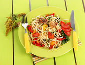 Noodles with vegetables on plates on wooden background — Stock Photo