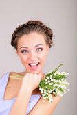 Young woman with beautiful hairstyle and flowers, on grey background — Stock Photo