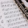 Musical notes and clarinet on wooden table — Stock Photo