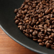 Black wok pan with coffee beans on wooden table, close up - Stock Photo