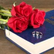 Wedding rings on bible with roses on wooden background — Стоковая фотография