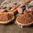 Cocoa powder in spoons and beans on wooden background - Stock Photo