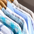 Men&#039;s shirts on hangers on gray background - Stock Photo