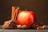 Cinnamon sticks,red apple, nutmeg,and anise on wooden table on brown background — Stock Photo
