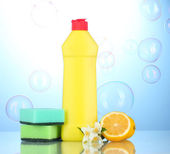 Dishwashing liquid with sponges and lemon with flowers on blue background — Stock Photo