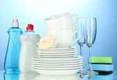 Empty clean plates, glasses and cups with dishwashing liquid and sponges on blue background — Stock Photo
