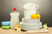 Empty clean plates, glasses and cups with dishwashing liquid, sponges and lemon on wooden table on grey background — Stock Photo