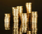 Many coins in columns on dark background — Stock Photo