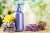 Liquid and hand-made soaps on wooden table, on green background — Stock Photo