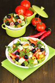 Greek salad in plate on wooden table — Стоковое фото