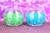 Glasses with colorful decorative stones on bright background — Stock Photo