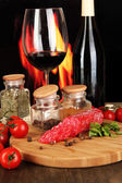 Tasty salami on board wooden table on fire background — Stock Photo