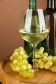 Composition of wine bottles, glass of white wine, grape on wooden barrel, on color background — Stock Photo