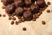 Chocolate candies and coffee beans, on beige paper background — Stock Photo