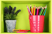 Colorful pencils in pail on shelf on pink background — Stock Photo