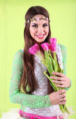 Young beautiful girl with decorative wreath on her head holding bouquet of flowers, on green background — Stock Photo