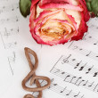 Treble clef and rose on musical background - Stock Photo