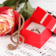 Treble clef, rose and box holding wedding ring on musical background - Stock Photo