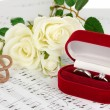 Treble clef, roses and box holding wedding rings on musical background - Stock Photo