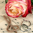 Treble clef, rose and wedding rings on musical background - Stock Photo