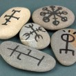 Fortune telling  with symbols on stones on grey background - Stock Photo