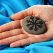 Fortune telling  with symbols on stone in hand on blue fabric background - Foto Stock