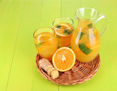 Orange lemonade in pitcher and glasses on wooden table close-up — Stock Photo