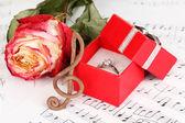 Σολ, τριαντάφυλλο και πλαίσιο κρατώντας το γαμήλιο δαχτυλίδι στο μουσικό υπόβαθρο — Φωτογραφία Αρχείου