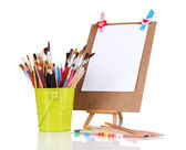 Small easel with sheet of paper with art supplies isolated on white — Stock Photo