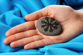 Fortune telling with symbols on stone in hand on blue fabric background — Stock Photo