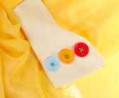 Three buttons on beige and yellow cloth — Stock Photo