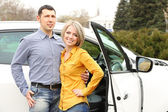 Portrait of happy beautiful couple standing near the car — Stock Photo