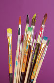 Many brush in paint on purple background — Stock Photo