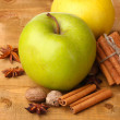 Cinnamon sticks, apples, nutmeg,and anise on wooden table - Stock Photo