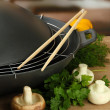 Stock Photo: Black wok pand vegetables on kitchen wooden table, close up