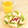 Tasty canapes with cheese and kiwi, cranberry, on color plate, on wooden background - Stock Photo